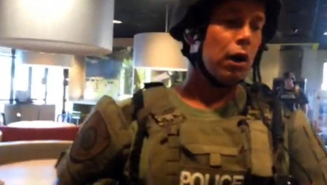 This image taken from video provided by Wesley Lowery of The Washington Post shows a police officer confronting Lowery in a fast-food restaurant in Ferguson, Mo., on Aug. 13, 2014. Lowery and Ryan Reilly of The Huffington Post were charged earlier this month with trespassing and interfering with a police officer's performance of his duties in relation to the incident. Police say the journalists didn't leave the restaurant fast enough.
