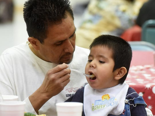 James Brown Jr. of Crouch Mesa feeds his son, Aiden Brown, 3, during the Community Christmas Dinner on Friday at the Aztec Senior-Community Center.