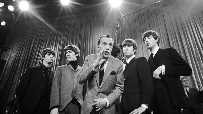 """Ed Sullivan, center, stands with The Beatles during a rehearsal for the British group's first American appearance, on the """"Ed Sullivan Show,"""" in New York on Feb. 8, 1964. From left:  Ringo Starr, George Harrison, Sullivan, John Lennon and Paul McCartney. The rock 'n' roll band known as """"The Fab Four"""" was seen by 70 million viewers. """"Beatlemania"""" swept the charts with 20 No. 1 hits and more than 100 million records sold.  The Beatles broke up in 1970."""