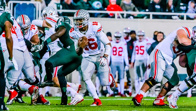 Ohio State quarterback JT Barrett (center) runs through a hole in the MSU line for a 1st down in the 1st quarter of  their game.