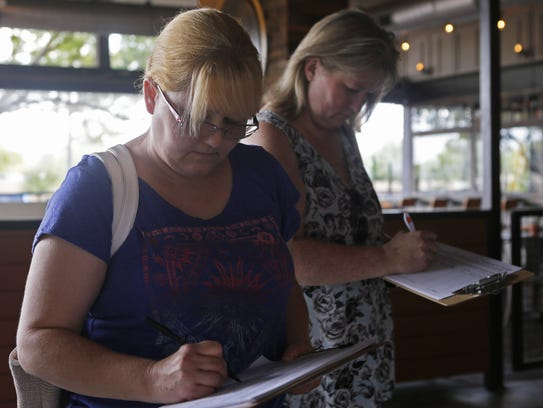 Terri Barkley (left) and Rochelle Kiggins sign a petition