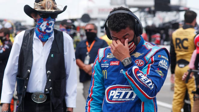 Driver Bubba Wallace, right, is overcome with emotion as he and team owner Richard Petty walk to his car in the pits of the Talladega Superspeedway prior to the start of the NASCAR Cup Series on Monday.