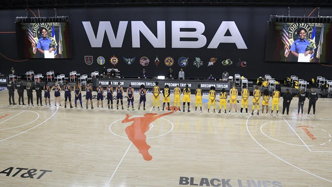 Members of the Phoenix Mercury, left, and Los Angeles Sparks stand for a moment of silence in honor of Breonna Taylor before a WNBA basketball game, Saturday, July 25, 2020, in Ellenton, Fla.
