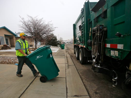 Armando Ortiz, a driver with Waste Management, carries a trash can to his truck on Wednesday on Wellington Street in Farmington.