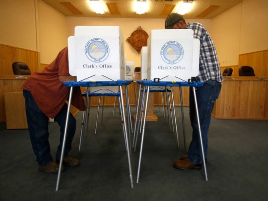 Two voters fill in their ballots on Tuesday at Farmington City Hall.