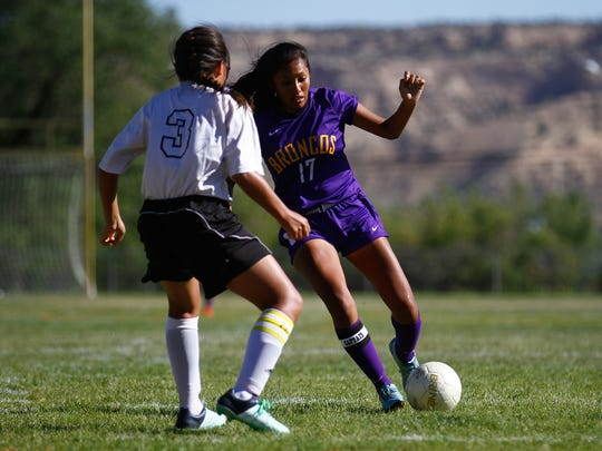 Kirtland Central's Nikki Begay moves the ball past Navajo Prep's Nizhoni Tallas during a Sept. 8 game at Eagle Stadium in Farmington.