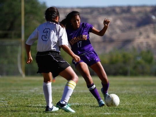 Kirtland Central's Nikki Begay moves the ball past Navajo Prep's Nizhoni Tallas during a Sept. 8 game at Eagle Stadium in Farmington.