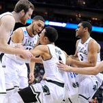 MSU's Bryn Forbes, center, is helped off the floor and is cheered by teammates Matt Costello, Denzel Valentine and Alvin Ellis II, left to right, after he hit a three point shot and was fouled late in the Spartans' 70-63 victory over Georgia during their NCAA game in Charlotte, NC Friday 3/20/2015. Forbes made the free throw for a four point play.