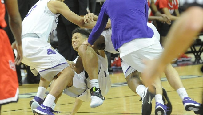 ACU players descend on Payten Ricks, center, after Ricks hit the game-winning shot from midcourt in the Wildcats' 67-64 victory over Lamar on Saturday, Jan. 14, 2017 at Moody Coliseum.