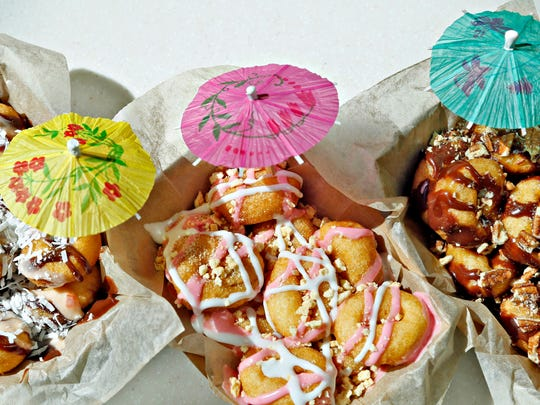 From left to right, Orange Coconut Cove, Strawberry Surf and Turtle Bay doughnuts from Mahalos Mini Donuts at the Jordan Creek mall.