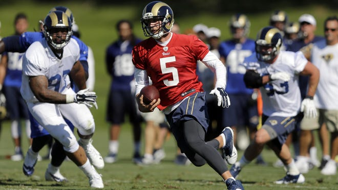 Rams quarterback Nick Foles (5) scrambles with the ball during training camp on Friday.