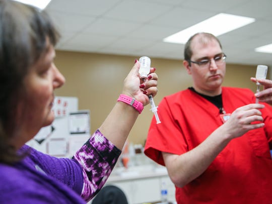 Instructor Gina Brown shows Justin Smith how to fill a syringe during a certified medical assistant class April 5 at Howard College.
