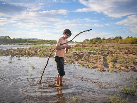 Las Cruces native Domingo Cadena, 14, searches for toads on the Rio Grande by Mesilla Valley Bosque State Park as water seeps into the river bed for the first time this year on May 27. Las Cruces native Domingo Cadena, 14, searches for toads on the Rio Grande by Mesilla Valley Bosque State Park.