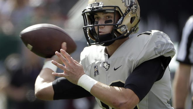 Central Florida quarterback McKenzie Milton throws a pass against South Florida during the first quarter of an NCAA college football game Saturday, Nov. 26, 2016, in Tampa, Fla. (AP Photo/Chris O'Meara)