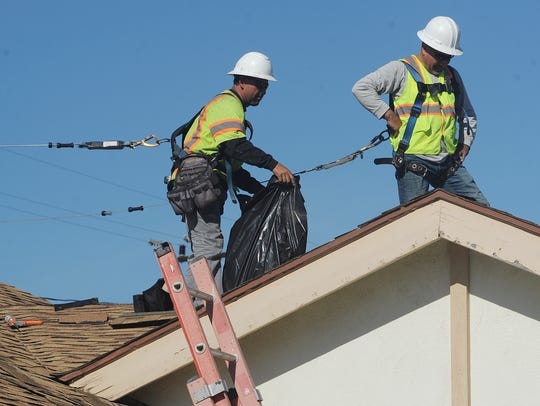 Roofers Gustabo Belmotes, left, and Jose Salgado make