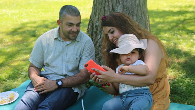 Hulika Aydin (right) and Anuj Gupta (left), with their son, Lincoln, look at a photo of the group. The family still figuring out their Father's Day traditions.