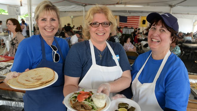 Helen Tassakin of Vineland, Pana Papamihalakis of Vineland, and Isabel Kaskabas of Vineland, from left, show off some of the food, a gyro, grape leaves, spanakopita, and tyropita, at the Greek Orthodox Church of St. Anthony's Greek Festival, Sunday, May 24, 2015 in Vineland.