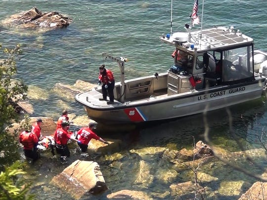 The U.S. Coast Guard and firefighters in Burlington transfer a woman onto the deck of a Coast Guard boat after she was rescued from the base of the cliff.