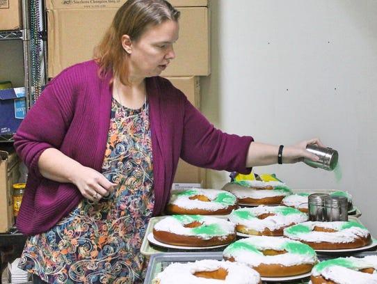 Lilah's Bakery owner Lisa Tike sprinkles Mardi Gras-colored