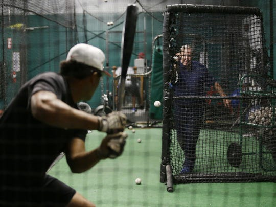 Hitting instructor Craig Wallenbrock (back) throws batting practice as a video camera records the swing of a college player on Saturday.