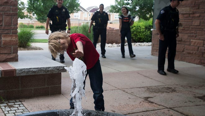 Officers, from left, Brian Werder, Kelsey Skaar and Scott Maher look on with Desiree Loban, center, as Loban's son Dravus Sullivan plays in one of the fountains outside of the police station on Thursday, June 7, 2018, at the Fort Collins Police Department on South Timberline Road in Fort Collins, Colo.