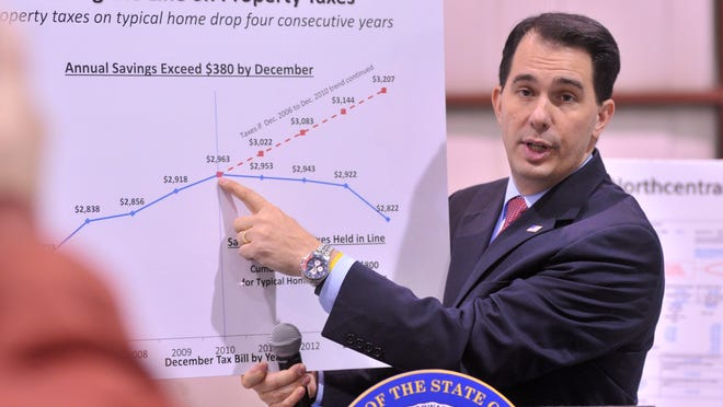 "Gov. Scott Walker points to a property tax graph on Wednesday during a visit to the Wausau Municipal Airport as part of his ""Property Tax Relief"" tour."