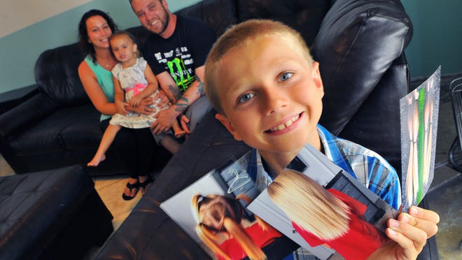 Christian McPhilamy, 8, of Melbourne shows photos of his hair he just cut 12 inches off to donate to a nonprofit, Children with Hair Loss. In the background is mom Deeanna Thomas, stepdad Scott Norris and sister Avalynn Norris, 3.