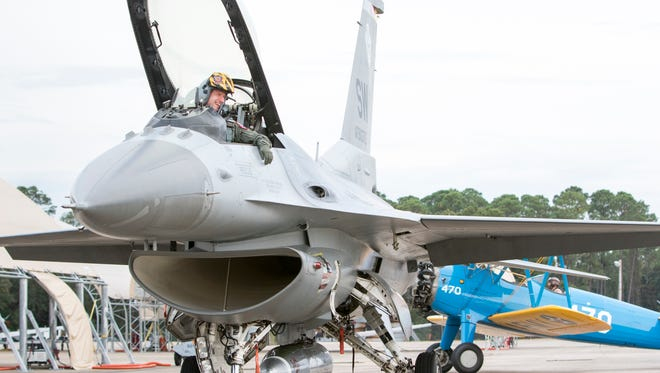 """A bi-plane taxis behind the Air Force F-16 Viper piloted by Major Craig """"Rocket"""" Baker at the Pensacola Naval Air Station on Wednesday, November 9, 2016.  The Viper demonstration team will perform as part of this weekend's airshow."""