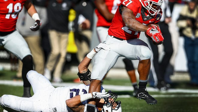 Georgia running back Nick Chubb (right) runs over TCU defender Niko Small (left) for a late fourth quarter touchdown during action of the 58th Annual AutoZone Liberty Bowl in Memphis, Tenn.