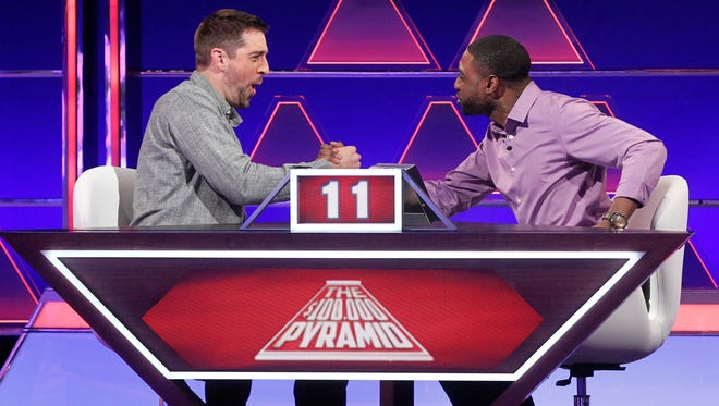 "Green Bay Packers quarterback Aaron Rodgers, left, and contestant Curtis Reed compete against FOX Sports sideline reporter Erin Andrews and contestant Brooke Snell at 9 p.m. Sunday on ""The $100,000 Pyramid."""