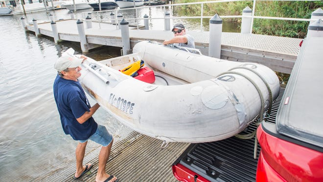 Fred Lcke, left, and Mike Gane load a dinghy onto their truck at the Mahogany Mill boat ramp in Pensacola on Wednesday, Sept. 6, 2017. They secured their boat in the water, but removed the dinghy to prepare for Hurricane Irma.