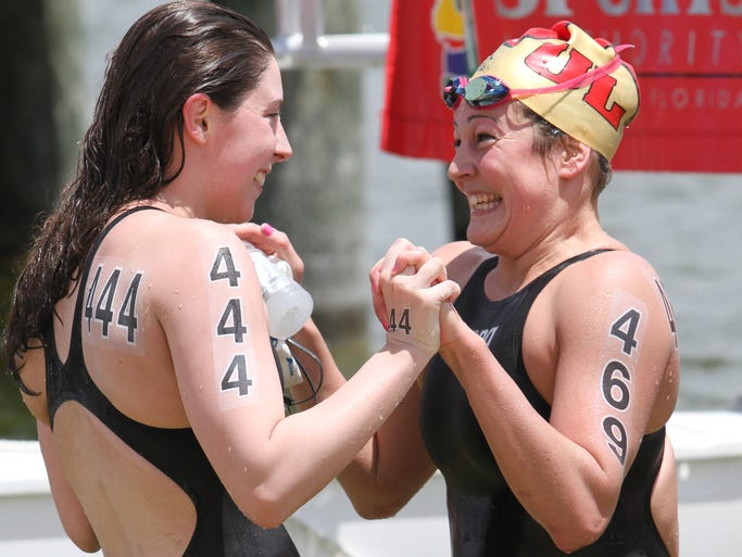 Professional marathon swimmers Jade Dusablon, left, of Canada,  and Leonie Pamerleau, of Canada, celebrate their finish during the the 2014 Open Water Festival at Miromar Lakes on Saturday.