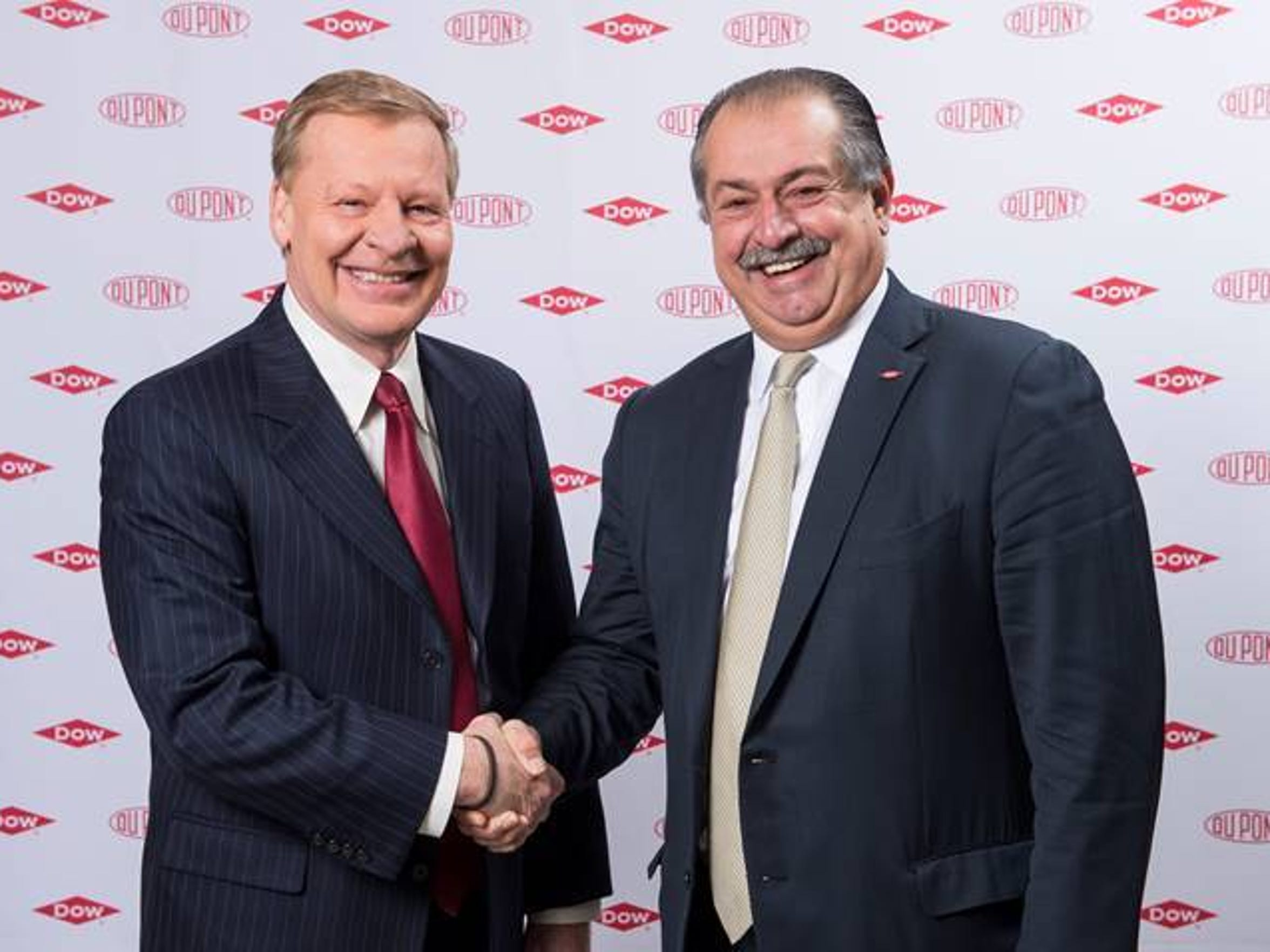 DuPont CEO Ed Breen (left) shakes the hand of The Dow Chemical Co. CEO Andrew Liveras to celebrate a merger between the two companies.