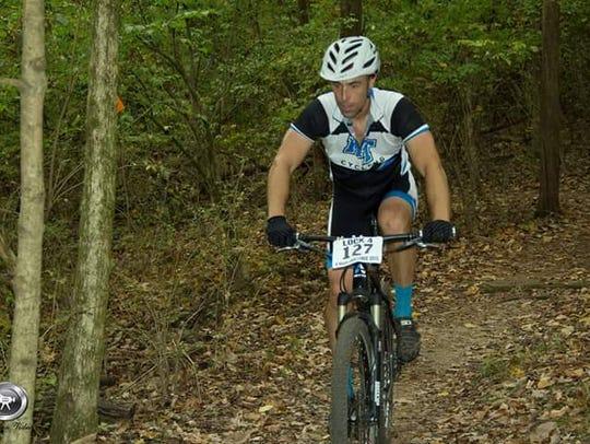 Josh Stone rides a mountain bike. Stone directs MTSU's