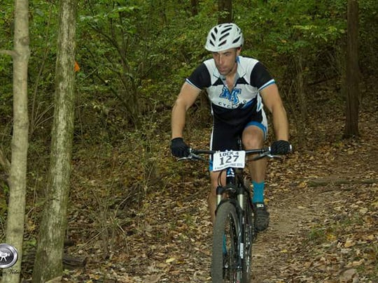 Josh Stone rides a mountain bike. Stone directs MTSU's
