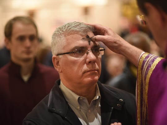 Archbishop Allen Vigneron places the ash on the forehead of parishioner David Bonitas, of Sterling Heights, during Ash Wednesday Mass at St. Aloysius in Detroit on Wednesday February 14, 2018.
