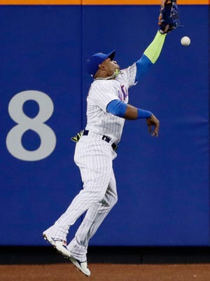 Mets left fielder Yoenis Cespedes leaps for a ball hit by Philadelphia Phillies' Maikel Franco for an RBI double during the third inning of a baseball game Thursday, April 20, 2017, in New York. Cespedes left the game early with an injury.
