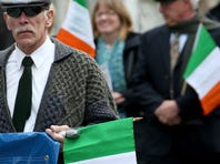 Ann McGuigan wipes away a tear as the names go the 16 martyrs are read during the ceremony  commemorating the Easter Uprising of 1916 in Ireland at Holy Sepulcher.