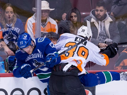Vancouver Canucks left wing Daniel Sedin (22) is checked by Philadelphia Flyers' Mark Alt during the second period of an NHL hockey game Thursday, Dec. 7, 2017, in Vancouver, British Columbia. (Jonathan Hayward/The Canadian Press via AP)