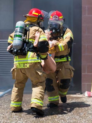 WIPP firefighters rescue a mannequin from a burning building during live-fire exercises.