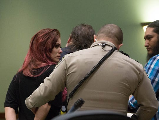 Josie Rubio,left, and Stephan Cordero, right, are handcuffed