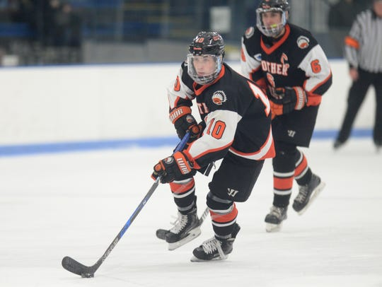 Brother Rice forward Nick Marone (10) moves the pucj