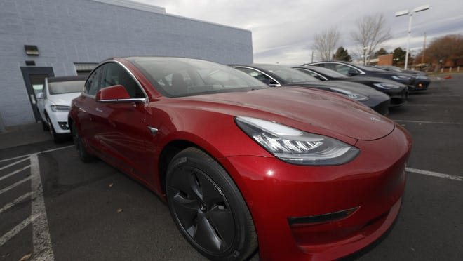 In this Nov. 10, 2019, photograph, a long row of unsold 2020 Model 3 sedans sits at a Tesla dealership in Littleton, Colo. Holland Department of Public Safety detectives are getting a new squad car that is likely to catch some attention -- a Tesla Model 3.