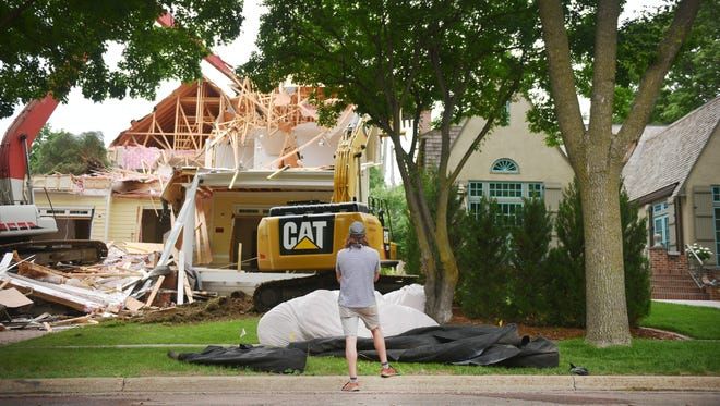 Jesse Deffenbaugh, residential designer who redrew plans for the McKennan Park home, watches the home come down Thursday, June 7, in Sioux Falls. Deffenbaugh stands between the Sapienza home, left, and the McDowell home, right. The McDowell's filed a law suit against the Sapienzas in 2015.