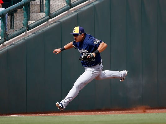 Milwaukee Brewers left fielder Ji-Man Choi, of South Korea, makes a catch on a sacrifice fly by Cincinnati Reds' Joey Votto during the second inning of a spring training baseball game Friday, March 16, 2018, in Goodyear, Ariz. (AP Photo/Ross D. Franklin)