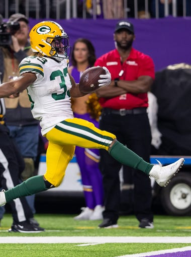 Dec 23, 2019; Minneapolis, Minnesota, USA;  Green Bay Packers running back Aaron Jones (33) rushes for a touchdown in the fourth quarter against Minnesota Vikings at U.S. Bank Stadium. Mandatory Credit: Brad Rempel-USA TODAY Sports