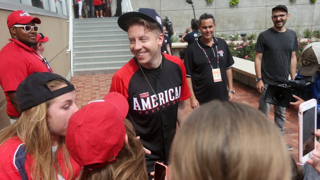Macklemore stops to talk with fans before taking batting practice for The All-Star Legends and Celebrity Softball Game at Great American Ballpark on Sunday, July 12.