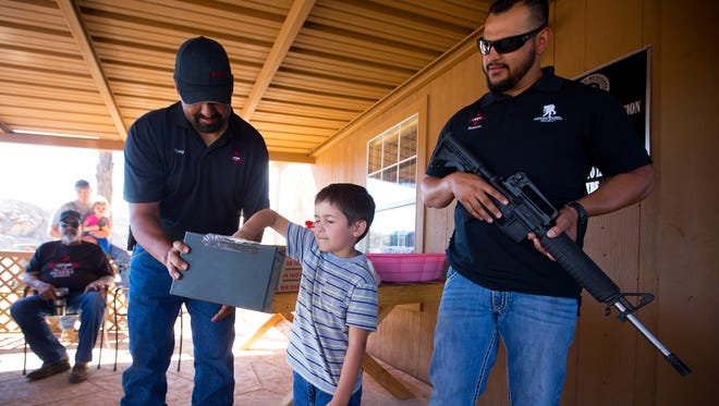 5-year-old Alexander Cook, son of Las Cruces Police Department Officer Erik Cook, pulls a raffle ticket out of an ammo box held by coyote hunting club New Mexico Desert Dogs co-founder Tony Torres, left, as fellow Dogs co-founder Ruben Olivas looks on at the The D.A.M. Ammo Co., Tuesday, August 16, 2016. The Desert Dogs organized the raffle, with the chance to win the AR-15 rifle held by Olivas, selling 150 tickets for $20 each, to help the family of slain Hatch Police Officer Jose Chavez.