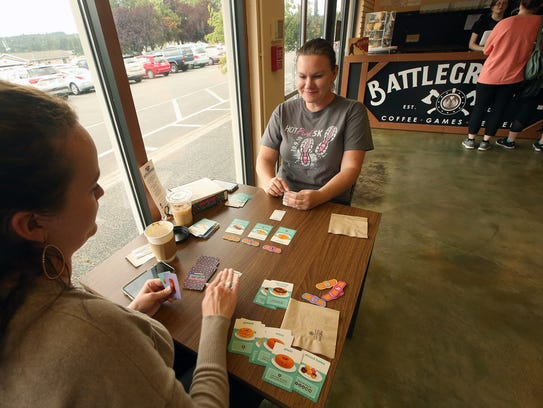 Elise Lee, of Poulsbo, left, and Stephanie Sutherlin, of Poulsbo, play the card game Go Nuts For Donuts at Battlegrounds Cafe in downtown Poulsbo on Thursday.