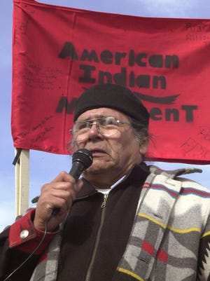 In this Feb. 27, 2003, file photo, Dennis Banks, one of the founders of the American Indian Movement, speaks to the crowd gathered to commemorate the 30th anniversary of the AIM standoff at Wounded Knee, S.D. The family of Banks says he died Sunday, Oct. 29, 2017, at the age of 80. Banks was a co-founder of AIM and a leader of the Wounded Knee occupation in 1973.